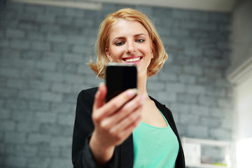 Young smiling woman holding smartphone in office