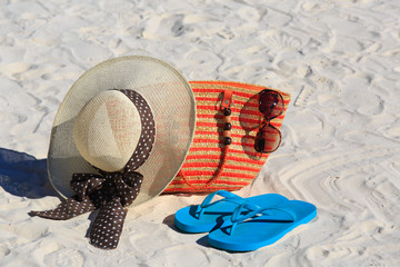 Straw hat, bag, sun glasses and flip flops on a sand beach