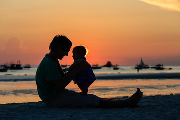 Silhouette of father and daughter on sunset beach