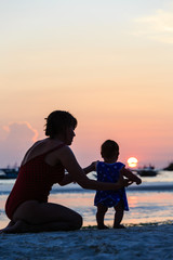 mother and daughter on sunset beach