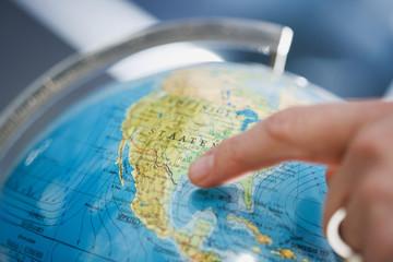 Person zeigt auf einem Globus