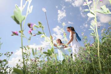 Zwei junge Frauen fangen Schmetterlinge