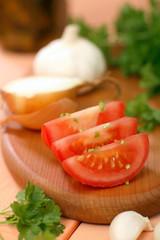 Tomatenscheiben, Zwiebeln, Knoblauch und Petersilie auf Schneidebrett