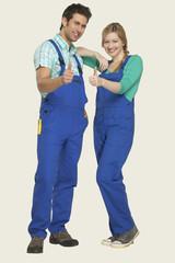 Mann und Frau in Overall zeigen Daumen hoch Zeichen, Lächeln, Portrait