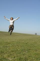 Frau springt auf der Wiese, Arme nach oben