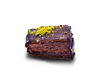 Slice of chocolate cake with pistachio nuts on white background