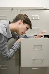 Geschäftsfrau suchen durch Aktenschrank, close-up