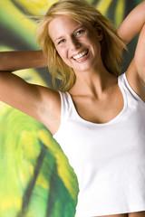 Blonde Frau freudestrahlend die Hände hinter dem Nacken
