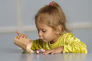 Kleines Mädchen spielt mit Würfeln