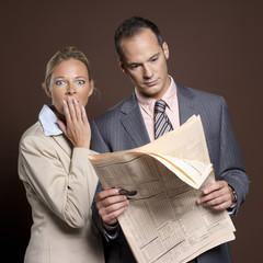 Geschäftsmann und Geschäftsfrau mit Zeitung, Frau bedeckte Mund