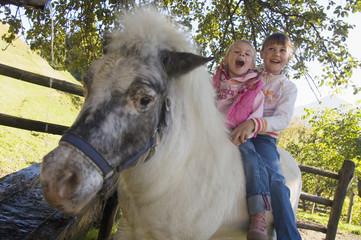 Zwei Mädchen sitzen auf Pony