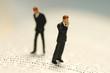 Zwei Figuren, Geschäftsmänner, auf Buch
