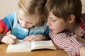 Junge und Mädchen sitzen am Schreibtisch und lernen