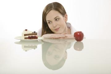 Junge Frau entscheidet sich, Kuchen oder Obst