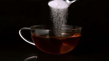 Teaspoon pouring sugar into cup of tea