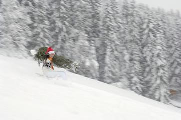 Junges Paar fährt Schlitten, mit Weihnachtsbaum