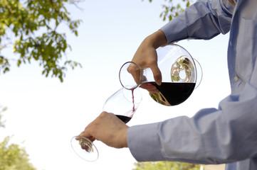 Kellnerin gießt Rotwein in ein Glas
