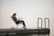 Geschäftsfrau sitzen im Schaukelstuhl auf Anlegestelle, mit Laptop, Seitenansicht