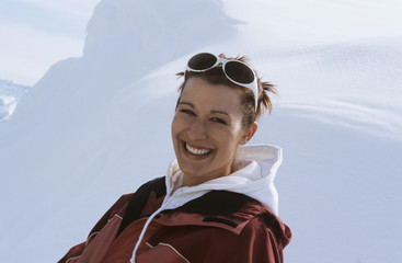 Junge Frau sitzt im Schnee, lächelnd