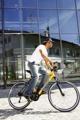 Deutschland, Bayern, Mann fährt Fahrrad, Seitenansicht
