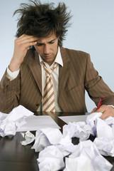 Geschäftsmann sitzen am Schreibtisch mit Papier zerknüllt, close-up