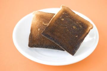 Zwei Scheiben Toast verbrannt auf Platte, close-up,