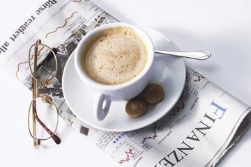 Tasse Kaffee und Brille auf Zeitung
