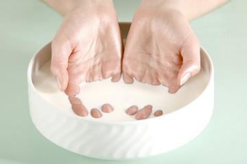 Hände einer jungen Frau in einer Schüssel Milch, Schönheit