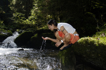 Österreich, Frau trinkt aus Bach im Wald