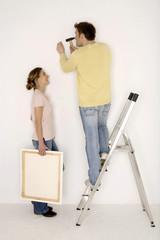 Junges Paar, Mann Hämmern Nagel in die Wand