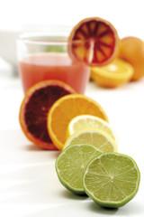 Verschiedene Zitrusfrüchte und ein Glas Saft