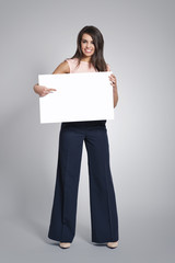 Happy woman pointing on empty whiteboard