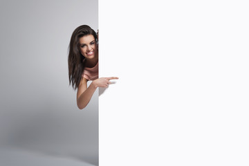 Happy woman pointing at copy space on whiteboard