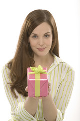 Junge Frau hält ein Geschenk, Geschenkpapier pink, Schleife grün
