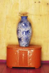 Blauer Vase auf roter Kiste vor gelber Wand