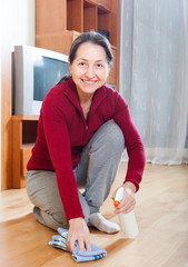 mature woman polishing parquet floor