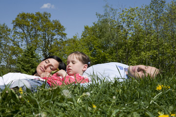 Eltern und Tochter entspannt auf der Wiese