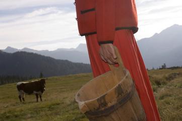Frau hält Milcheimer, Kuh im Hintergrund