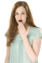 Junge Frau, die Hand auf dem Mund, erschrocken, ertappt