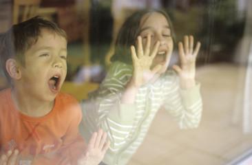 Kinder hinter Fensterscheibe