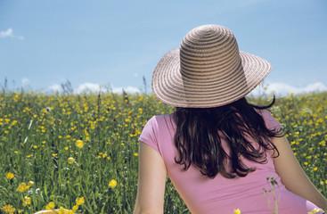Frau sitzt in Blumenwiese, Rückansicht