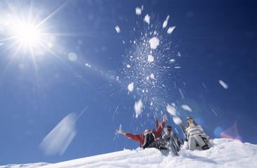 Drei Leute, die Spaß im Schnee haben