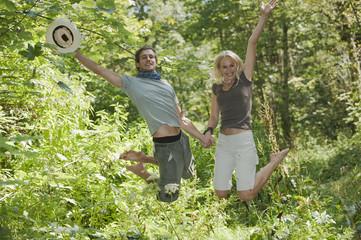 Junges Paar Händchen haltend, springt im Wald