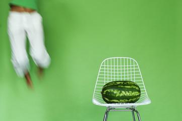 Junge Frau springt neben Stuhl mit Wassermelone, gesund und fit