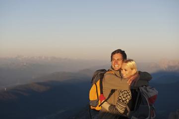 Österreich, Steiermark, Dachstein, Junges Paar umarmt sich auf dem Berg, lächelnd
