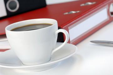 Tasse Kaffee vor Ordner