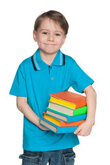 Cheerful clever little boy with books