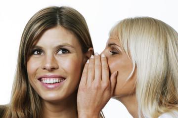 Zwei junge Frauen tuscheln, flüstern, lästern