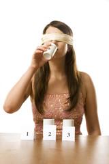 Junge Frau mit Augenbinde beim Geschmackstest, Produkttest