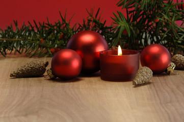 Weihnachtsdekoration mit brennender Kerze und Christbaumkugeln